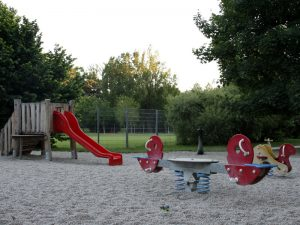 Rutsche udn Wippe mit Sand am Kleinkinderspielplatz im Auer Welsbach Park