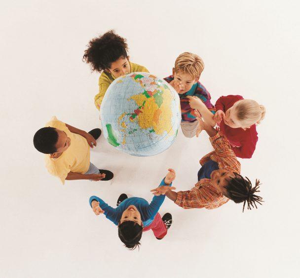 Kinder spielen mit einem Luftball, der wie eine Weltkugel aussieht.