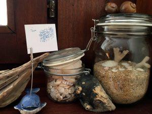 Jahreszeiten-Ecke mit Sommer-Glas voll mit Muscheln und Sand